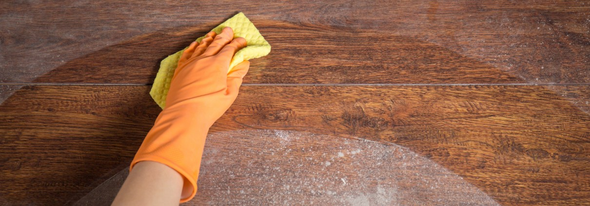 Cleaning soiled parquet in gloves with yellow rag